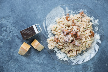 Risotto with chanterelle mushrooms and parmesan cheese over blue stone background, above view, horizontal shot