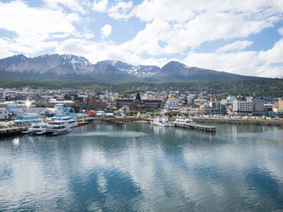 The town and docks of Ushuaia Argentina photographed from the bay. The cloudy sky is reflected in the water.