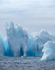 Iceberg with light and medium turquoise blues in a deep blue Southern Ocean. Cloudy sky is above. The icebergs have fissures, crevices and caves.