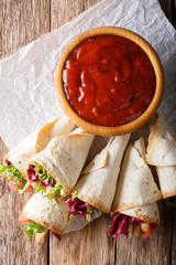 Freshly cooked burritos with turkey, lettuce and vegetables close up on a paper. Vertical top view