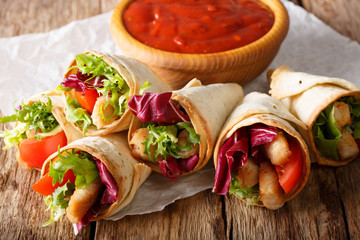 Freshly cooked burritos with turkey, lettuce and vegetables close up on a paper on the table. horizontal