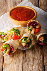 Delicious burrito with turkey, lettuce and vegetables close-up. vertical