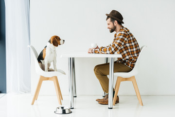 side view of man and cute beagle sitting at table