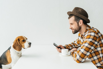 side view of man holding smartphone at table with dog