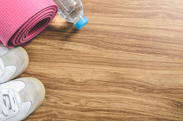 Sport shoes yoga mat and a bottle of water on wooden background.
