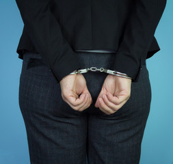 A business woman with cuffs in front of her. Arrested for crime