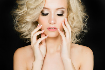 Beautiful curly hair. Girl with wavy blonde hair. Portrait of a young girl with a beautiful professional make-up. Bright make-up of eyes and lips.