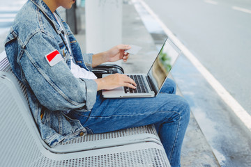 Asian young man sitting on the chair at the airport payment using credit card and laptop.