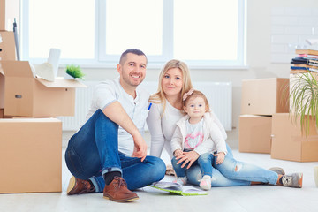 A happy family moves to a new apartment. Mother, father and child with boxes in the room of the new house.