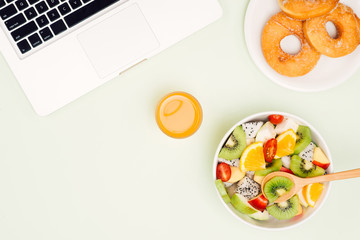 Healthy business lunch in office, fruit salad bowl near laptop on white background. Organic meal and donuts. Snack at break time.