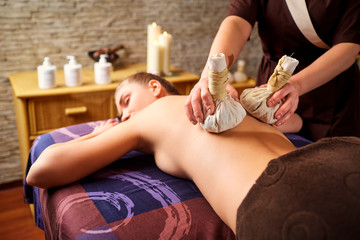 Close-up of a girl massage with bags in spa salon.