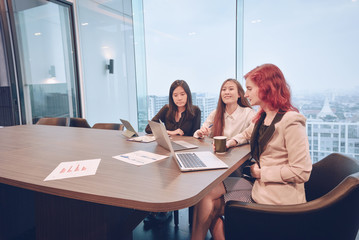 Group of business women meeting in a meeting room with blank screen, sharing their ideas, Multi ethnic
