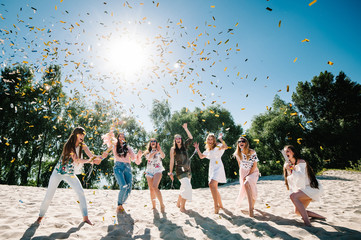 Beautiful happy stylish sexy young girls stand in beach and opens colored confetti on background nature. Party  Style boho. Maiden evening Hen-parties. Bachelorette. Close up. Portrait. Place for text