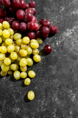 White and red grapes on a black aged background..