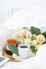 Morning in bed. Tray with bouquet, coffe and candle. Portrait