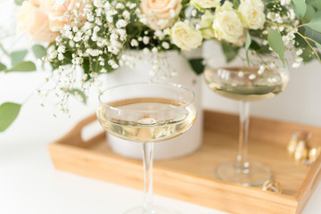 Cream wedding bouquet with roses, baby's breath and eucaluptus in wooden tray with wineglasses