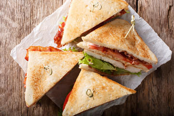 layer club sandwich with turkey meat, bacon, tomatoes and lettuce macro. Horizontal top view