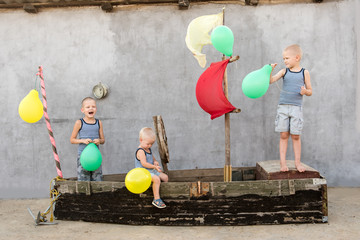 Happy boys play pirates and sailors. Three brothers have fun together. The old boat is decorated with balloons. Romantic adventure at the end of a summer day. Fun holidays in village yard