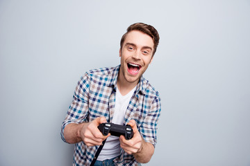 Portrait of crazy, cheerful, attractive, positive, very excited guy in checkered shirt holding joystick and playing video games with wide open mouth over grey background