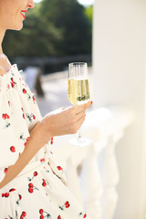 Woman holding glass of champagne. Party with sparkling champagne glasses outdoors