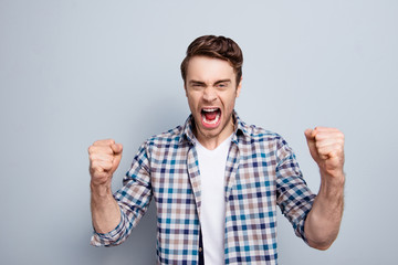 Aggressive man in checkered shirt with raised fists and open mouth is out of himself, yelling, screaming, shouting with cruelty over grey background