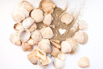 Heart drawn on the sand on the beach among seashells. Vacation, beach.