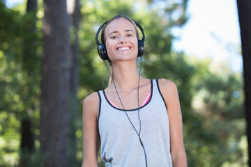 young woman listening music with headphone in nature
