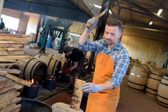 cooper cutting wood for smoking barrels