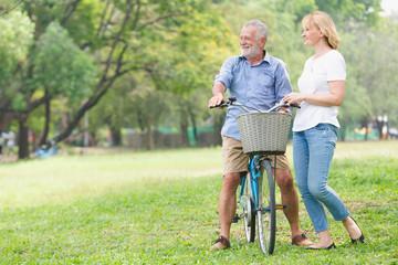 Senior couple walking their bike along happily talking happily.