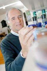 man choosing jar from shelf