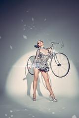 sexy lady im spiegelkostüm  mit einem rennrad auf der schulter, welches aus spiegelkugeln besteht.