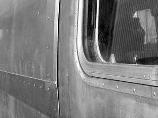 Aluminiumhaut mit Nieten und Fenster eines alten amerikanischen Wohnwagen im Gewerbegebiet in Hamburg, fotografiert in traditionellem Schwarzweiß