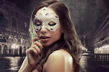 Beautiful brunette with Venetian mask. Young and beautiful woman on Venetian view background.