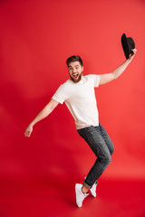 Excited bearded man dancing wearing hat. Looking camera