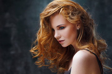 Excellent curly hair. Happy beautiful redheaded girl. Studio portrait on textured background.