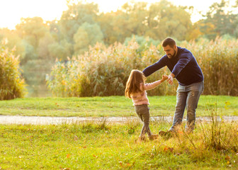 Dad and daughter in the autumn park play laughing