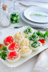 Stuffed eggs - with red fish, cheese and green cucumber on a white plate, selective focus
