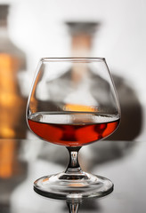 A glass of cognac on the background of two bottles