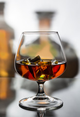 A glass of cognac with ice against the background of two bottles