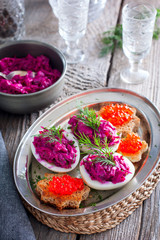 Snack of stuffed eggs with beets and fish filling on a wooden table, rustic style, selective focus