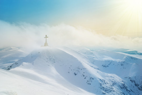 Mountain peaks covered by snow and Heroes cross on top of Bucegi illuminated by sunset light in winter season