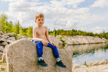 blond boy sitting on big rock on the rocky shore of the lake