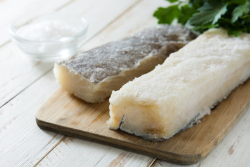Salted dried cod on white wooden table. Typical Easter food