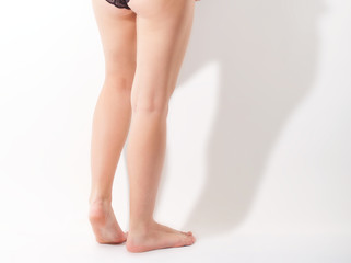 Cropped image of young woman in black panties.
