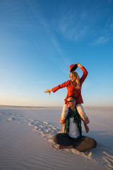 Joyful crazy couple, man with a expressive girl on his shoulders, sits in desert