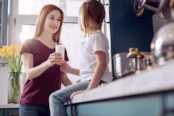 Favorite healthy drink. Charming young woman giving a glass of milk to her little daughter sitting on the kitchen counter and smiling at her lovingly