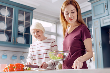 Healthy dish. Charming young woman and her elderly mother making a salad together, the younger woman holding a bowl with vegetables while the older one cutting