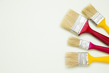 Painting the house. Two red and two yellow paint brushes on white background with copy space, top view, flat lay