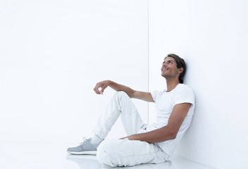 dreamy young man sitting beside a white wall.