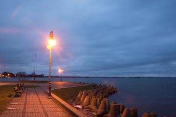 Pier at the Niegocin lake and rainy clouds at night in Gizycko, Masuria, Poland